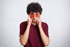 Thoughtful focused male with crisp hair, has serious concentrated expression, wears red sunglasses, isolated over white background. People, facial expressions Stock Photography