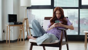 Thoughtful focused young woman getting insight and writing messages using cell phone sitting on chair in light apartment
