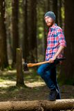 Thoughtful forester with an ax near a dumped tree. In the forest Royalty Free Stock Photo