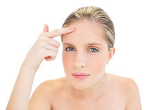 Thoughtful fresh blonde woman pointing her brow with her finger Royalty Free Stock Photos