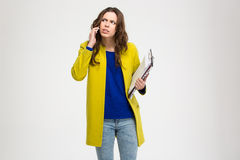 Thoughtful frowning young woman holding clipboard and using smartphone Royalty Free Stock Image