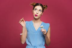 Thoughtful funny young woman guessing fortune using white flower Royalty Free Stock Image
