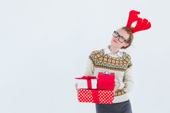 Thoughtful geeky hipster holding presents Royalty Free Stock Photos