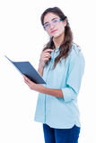 Thoughtful geeky hipster with a pen against her chin checking her notebook Royalty Free Stock Photo