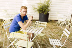 Thoughtful ginger male waiting at a table outdoors. Thoughtful handsome ginger male waiting at a table outdoors Stock Images