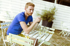 Thoughtful ginger male waiting at a table outdoors Stock Images