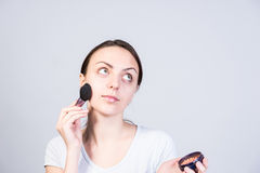 Thoughtful Girl Applying Makeup on Face with Brush Royalty Free Stock Photo