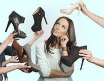 Thoughtful girl with assortment of shoes Royalty Free Stock Photos