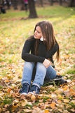 Thoughtful girl  in autumn park Royalty Free Stock Photography