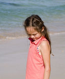 Thoughtful girl on beach. Young girl standing on beach looking at sand with thoughtful expression Stock Photography