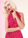 Thoughtful girl in blond wig and retro red dress winking. Pinup. Stock Photos