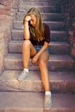 Thoughtful girl with blue eyes sitting at stone brick stairs Royalty Free Stock Photography