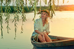 A thoughtful girl in a boat at the sunset. A dreaming beautiful woman with blond hair in a flower wreath is sitting in a boat at the sunset royalty free stock image