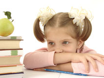 Thoughtful girl with books. Thoughtful young girl looking at pile of books with apple on top; isolated on white background Royalty Free Stock Image