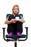 Thoughtful girl on chair holds cup tea or coffee. Royalty Free Stock Photo