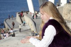 Thoughtful girl child on the waterfront. Thoughtful girl child standing on the waterfront looking down Stock Images
