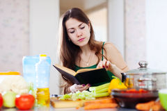 Thoughtful girl cooking with cookbook. In the kitchen at home Stock Photos