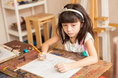 Thoughtful girl drawing for art class royalty free stock photos
