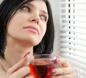 Thoughtful girl drinking tea at the window Royalty Free Stock Images