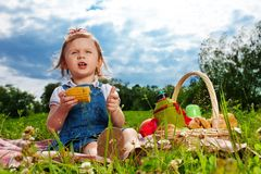 Thoughtful girl eating corn on picnic Stock Photography