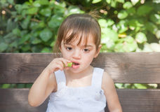 Thoughtful girl eating cucumber Royalty Free Stock Photos
