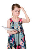 Thoughtful girl in a flowered dress with a Tablet PC Royalty Free Stock Images