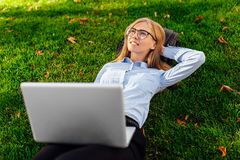 Pensive girl in glasses lying on the grass in the park with a laptop computer, dreams of something royalty free stock image