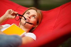 Thoughtful girl with glasses rests in hammock Royalty Free Stock Images