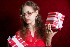 Thoughtful girl in glasses with two striped gift box Stock Image