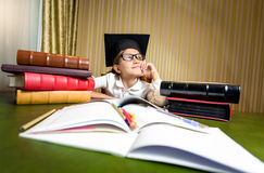 Thoughtful girl in graduation cap dreaming while sitting at tabl Stock Images