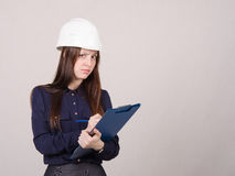 Thoughtful girl a helmet writes in pencil folder Royalty Free Stock Image