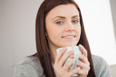 Thoughtful girl holding a cup of coffee and looking at camera Stock Photo