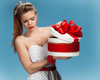Thoughtful girl holding holiday or birthday presents, gift box on blue background. Holidays, celebration, birthday concept Royalty Free Stock Photos
