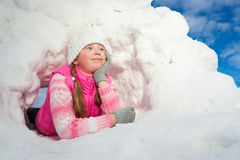 Thoughtful girl laying at the snow hole Stock Photos