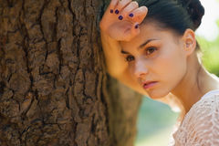 Thoughtful girl lean against tree Royalty Free Stock Images