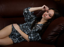 The thoughtful girl lies on a sofa Stock Photography