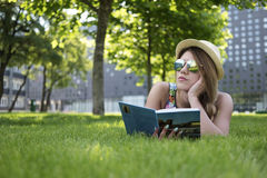 Thoughtful Girl Lying on the Green Grass with Book Stock Images