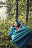 Thoughtful girl lying in a hammock and strumming the guitar melo. Thoughtful pretty girl lying in a hammock and strumming the guitar melody, a summer evening in Royalty Free Stock Photos