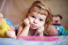 Thoughtful girl lying and looking at camera Stock Images