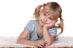 Thoughtful girl lying on the thick carpet Stock Images