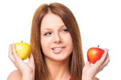 Thoughtful girl makes a choice between apples Stock Image