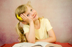 Thoughtful girl with open book Royalty Free Stock Photos