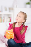 Thoughtful girl with piggy bank Stock Image