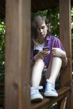 Thoughtful girl in a plaid shirt reads the news on the phone sit Royalty Free Stock Image