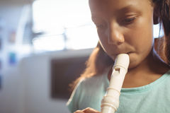 Thoughtful girl playing flute in classroom Stock Photo