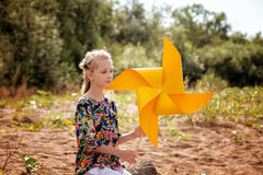 Thoughtful girl posing with paper windmill Stock Images