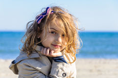 Thoughtful girl in raincoat on beach portrait Stock Photos