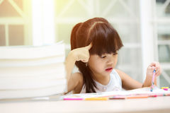 Thoughtful girl reading a book and using her imagination. Royalty Free Stock Photo
