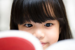 Thoughtful girl reading a book and using her imagination. Royalty Free Stock Image