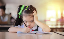 Thoughtful girl reading a book and using her imagination. Stock Photos